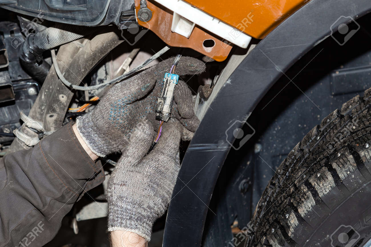 Close-up on the hands of the master in protective gloves connecting the connector with the wires in the electrical circuit of the car under the bumper near the orange wing in the workshop auto service - 120638952