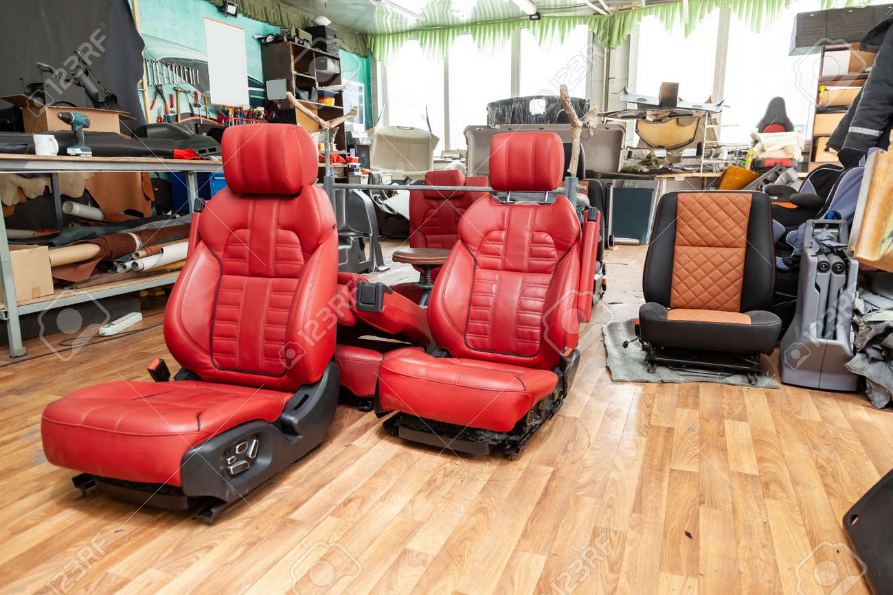 Four sport seats with red leather trim, located on the floor in the workshop for repair and tuning of cars and vehicles - 127027406