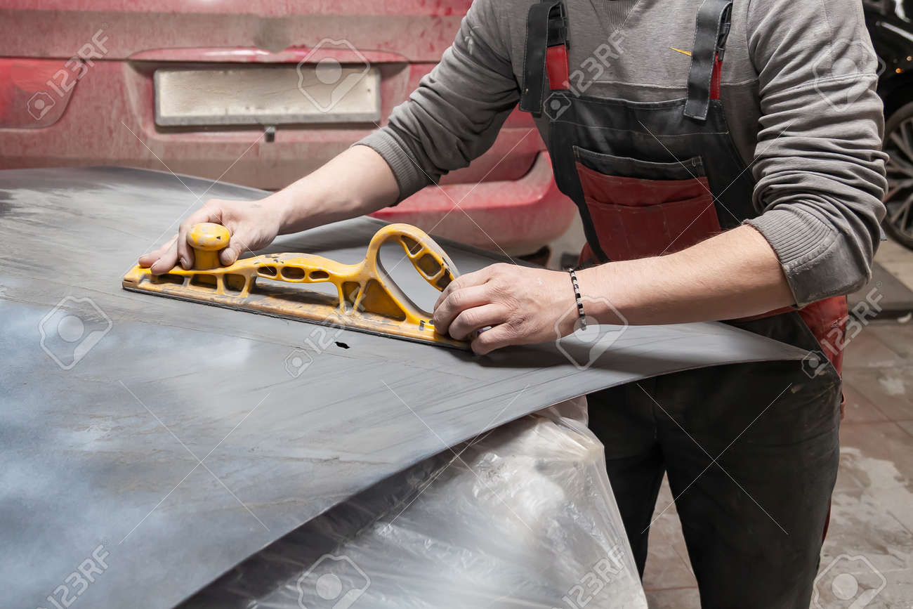 Man worker preparing for painting a car element using emery sender by a service technician leveling out before applying a primer after damage to a part of the body in an accident in vehicle workshop - 128336110