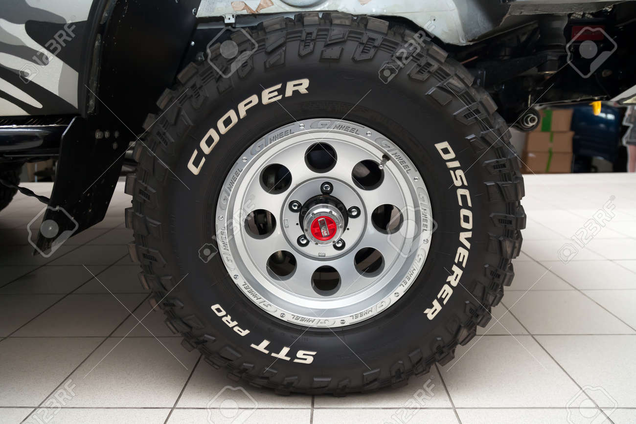 Novosibirsk, Russia - 02.26.2020: The most extreme all-season, off-road tire Cooper Discoverer STT Pro with AVM hubs off-road performance, tread design, tire durability on the wheel disk. - 141315404