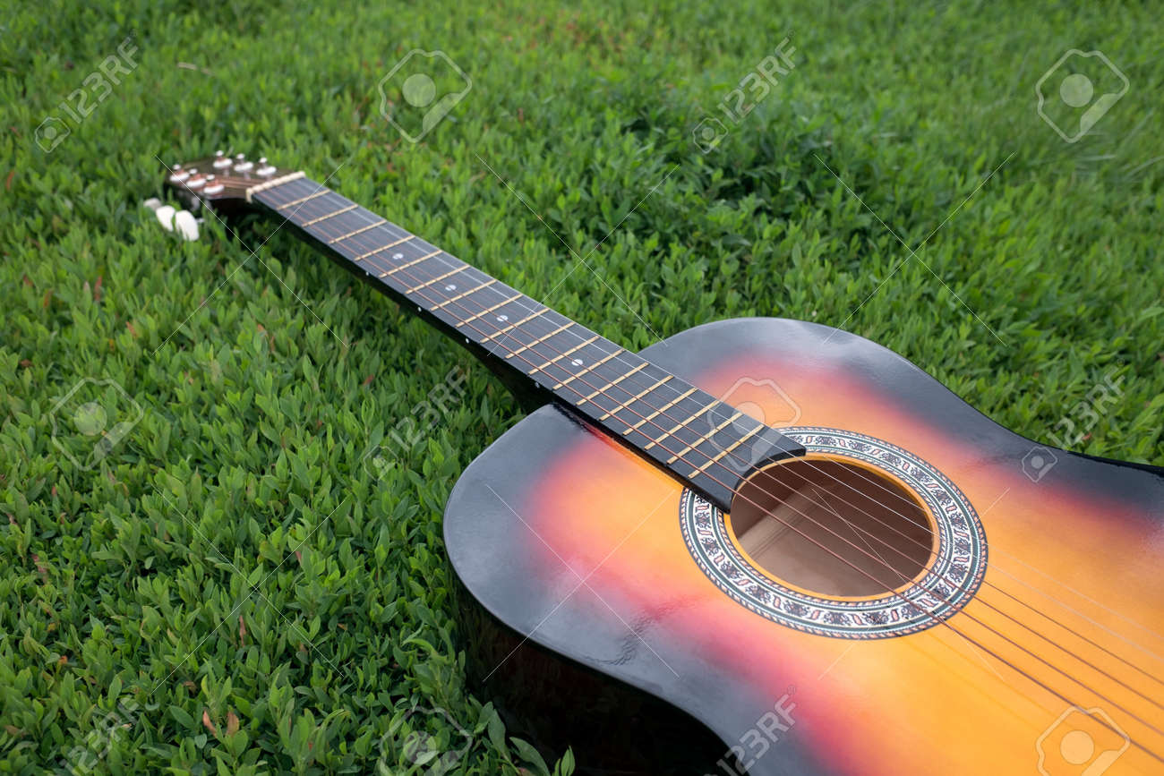 Acoustic Guitar Lying In The Green Grass In Summer In Daylight Stock