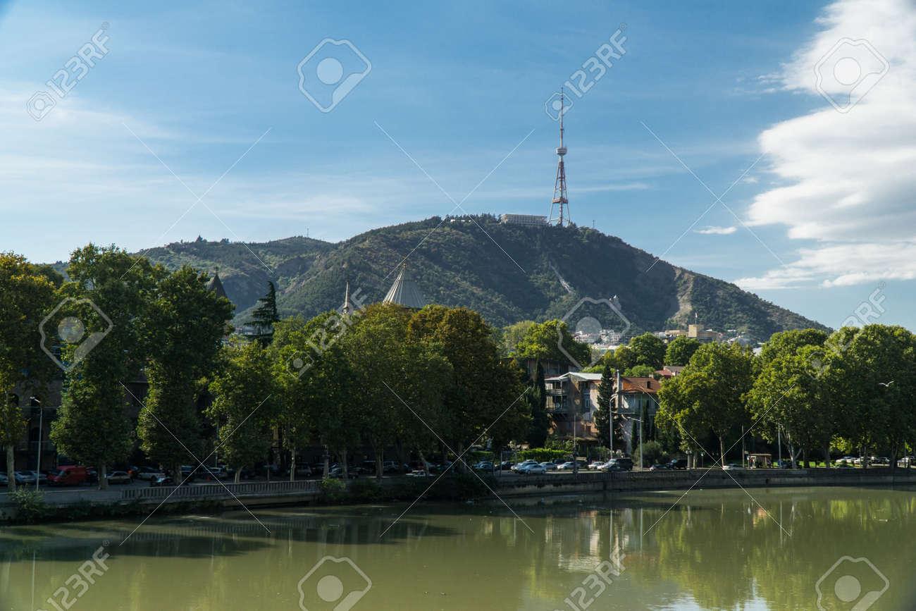 View of mount Mtatsminda through the Kura river in Tbilisi, Georgia. - 77580374
