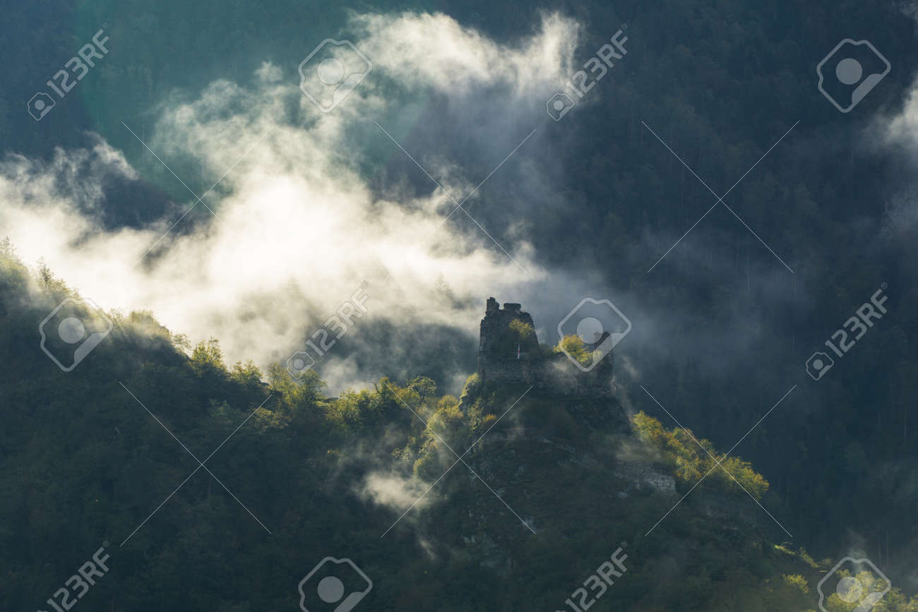 Morning mist around the ruins of a watchtower in the vicinity of Borjomi, Georgia. - 77010482