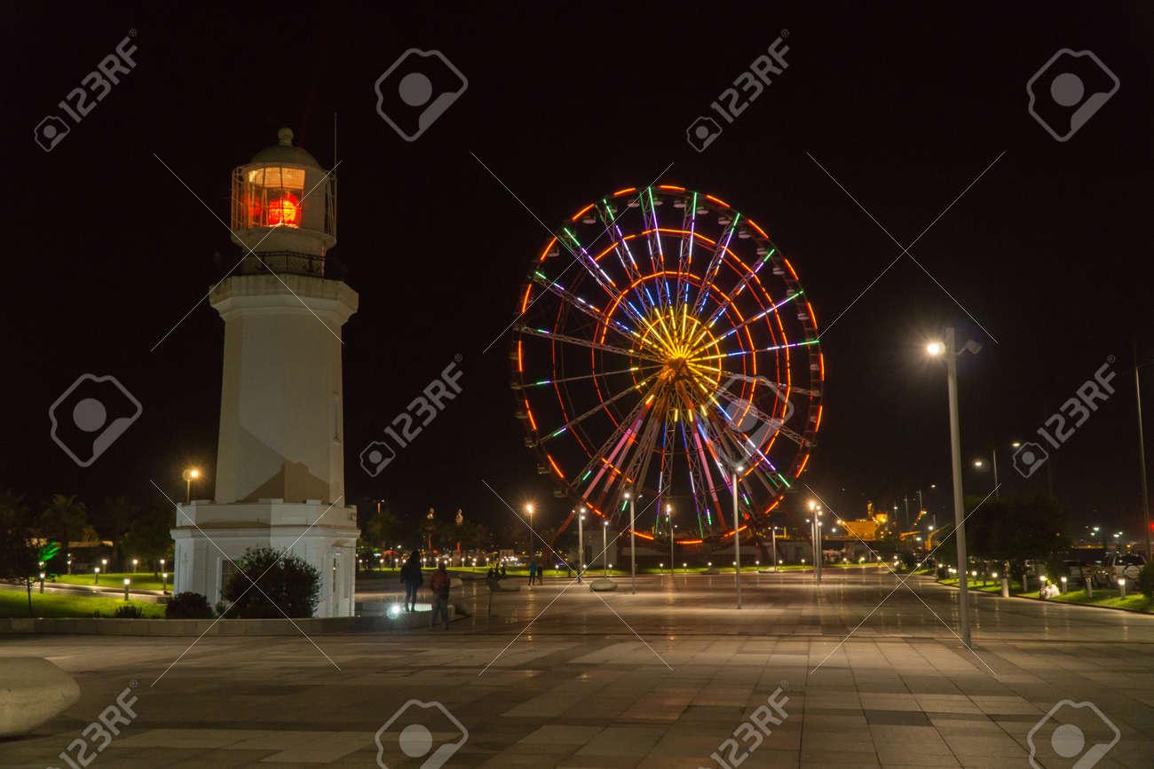BATUMI, GEORGIA - OCT 7, 2016: Night view of Batumi. Ferris wheel and lighthouse on seaside boulevard. - 77282288