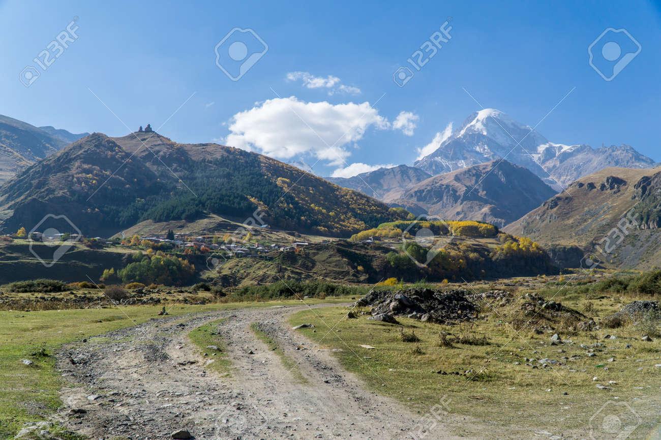 View of village Stepantsminda, Gergeti Trinity Church and mount Kazbek in Sunny weather - 77008092
