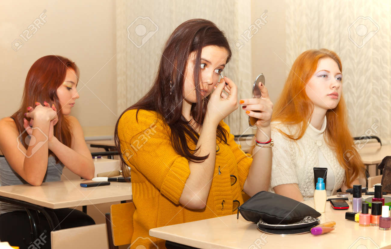 lassroom girls Stock Photo - girls in the classroom during recess apply makeup