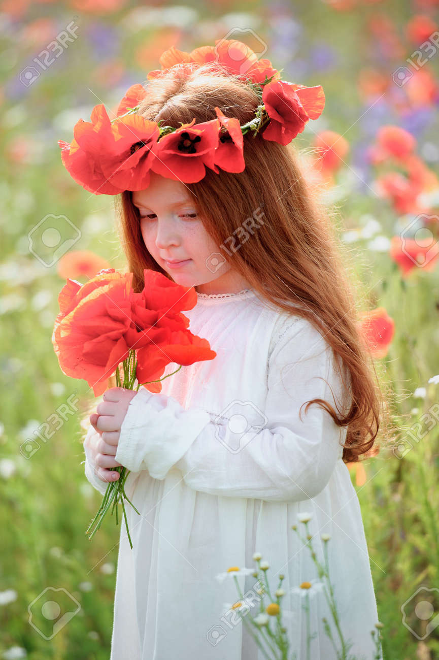 Little redhead girl with white dress on the green wheat field little redhead girl with white dress on the green wheat field with poppies wearing a flower izmirmasajfo Gallery