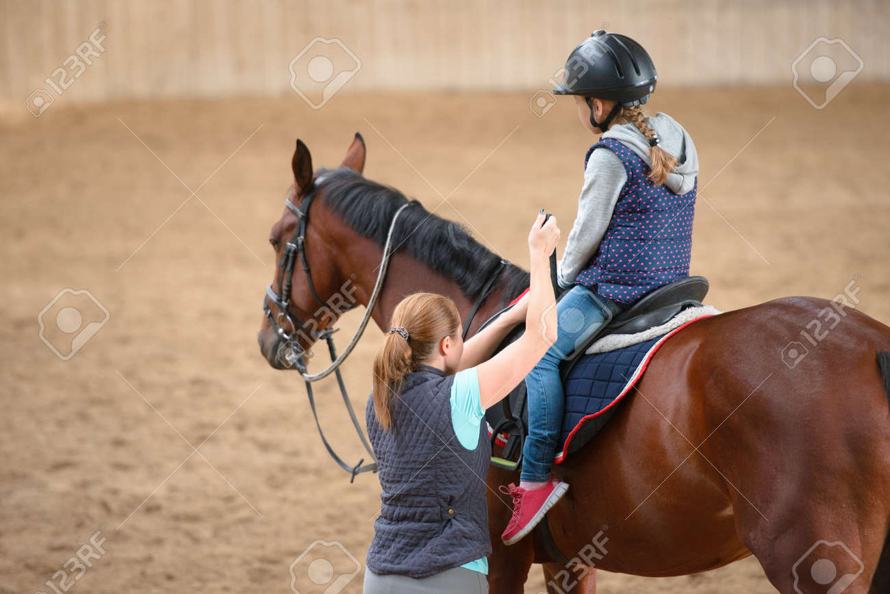Girl in helmet Learning Horseback Riding. Instructor teaches teen Equestrian. - 74152176