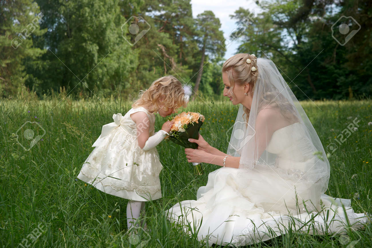 7099b8a7be866 mother in her wedding dress holding a wedding bouquet with little..