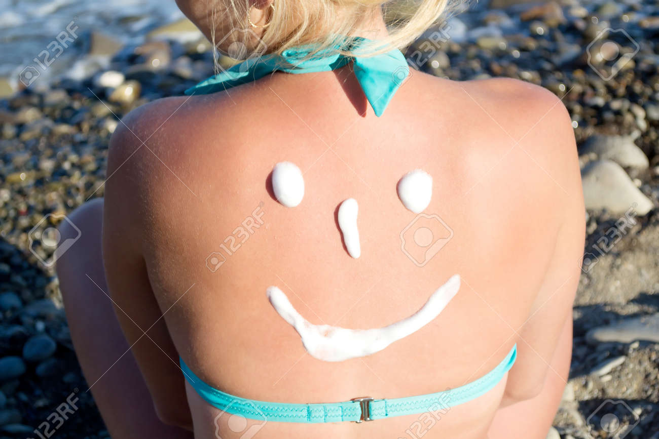 sun protection cream on her back - 15038395