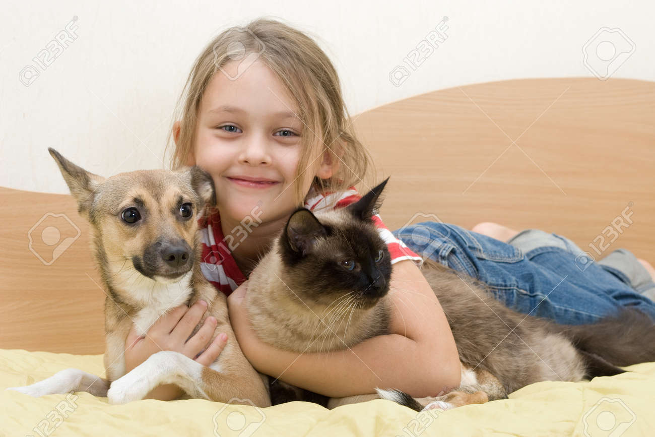 girl with pets on a bed of yellow color - 22441626