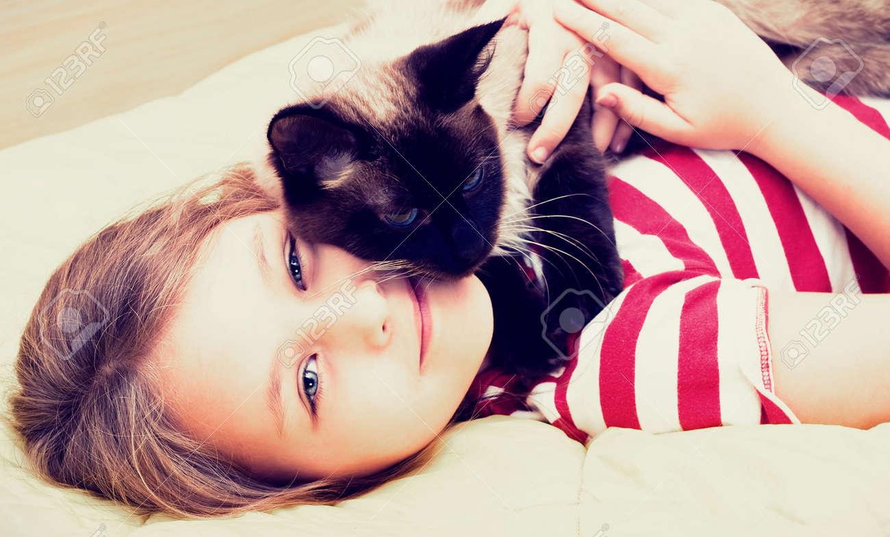 little girl hugging a cat - 27724214