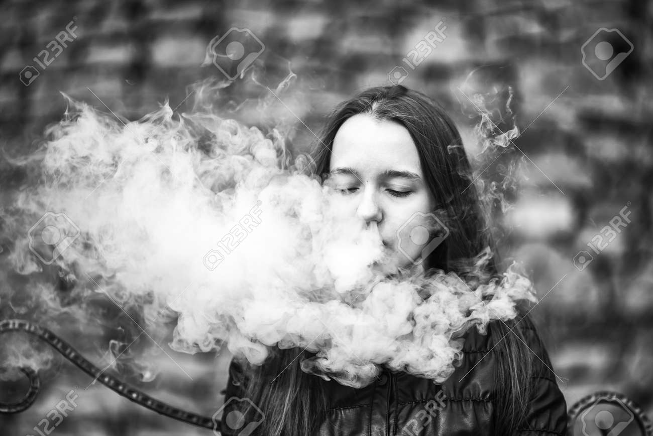 Stock photo vape a young beautiful white girl is sitting on a vintage bench and is smoking an electronic cigarette lifestyle black and white photo