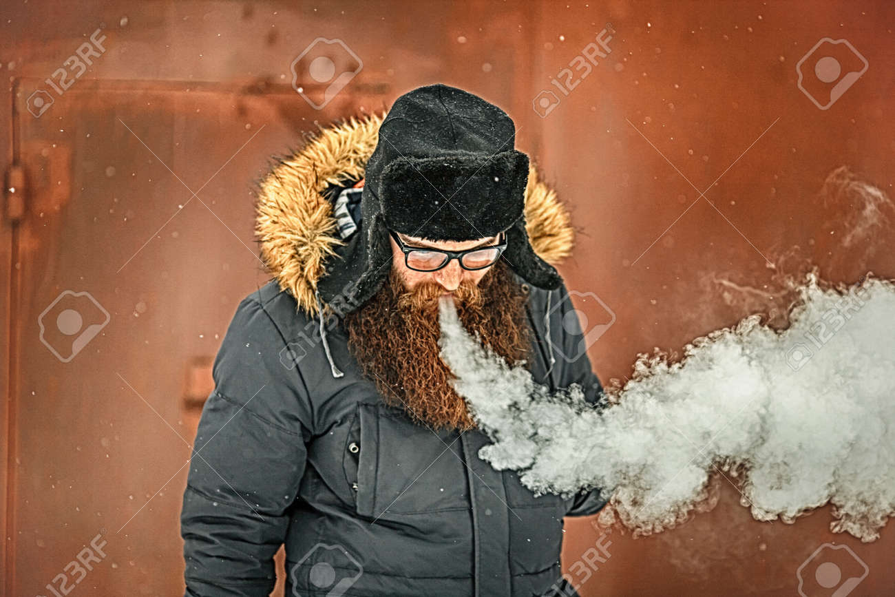 Vape bearded man in real life  Portrait of young guy with large