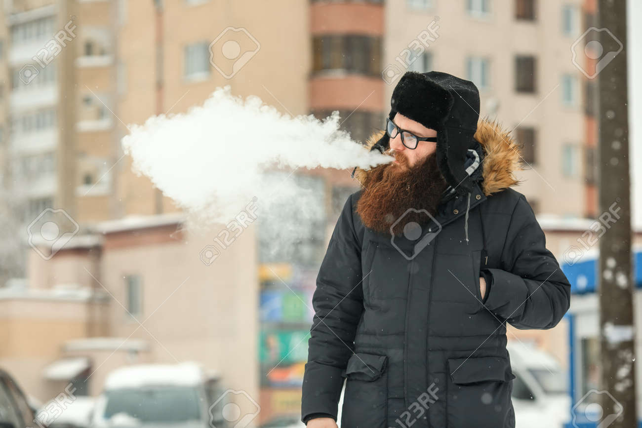 bf6cf25a484 Stock Photo - Vape bearded man in real life. Portrait of young guy with  large beard in glasses and a black cap vaping an electronic cigarette and  letting ...