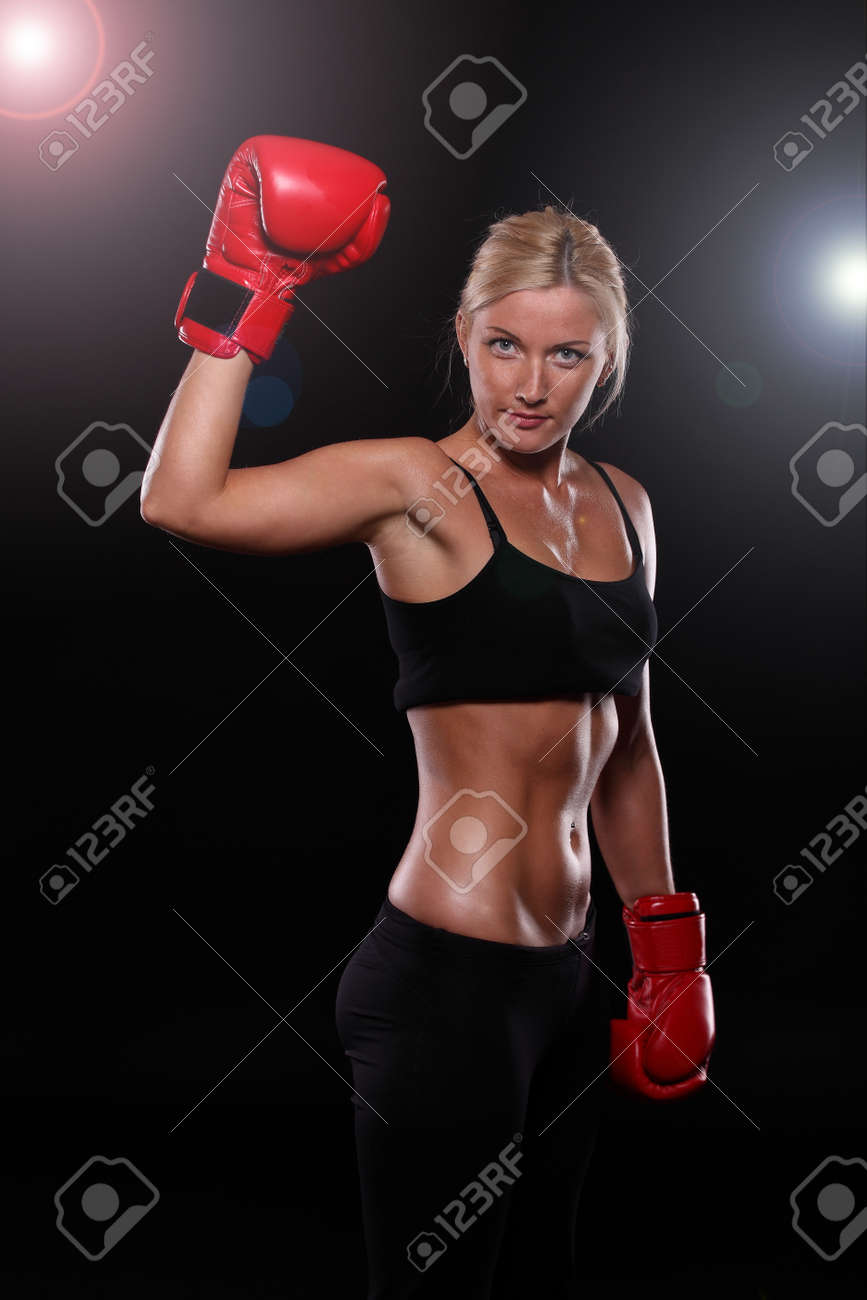Young woman wearing boxing gloves isolated on black Stock Photo - 24204441