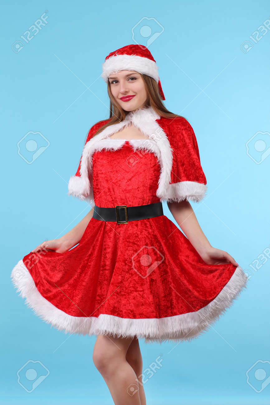 Christmas Suit.Beautiful Sexy Girl In A Christmas Suit Posing On A Blue Background