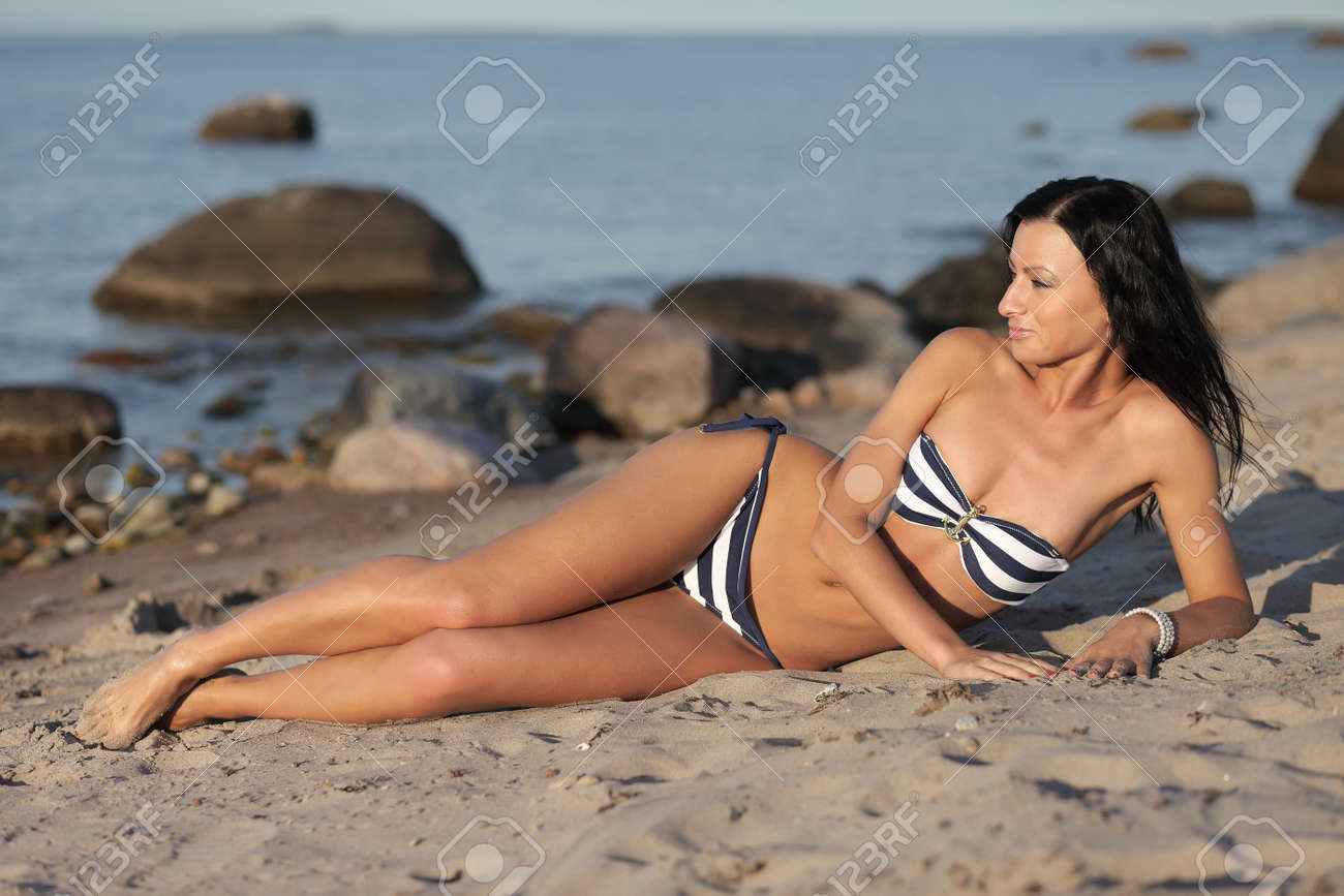 Stock Photo Young Tanned Girl On A Wild Wild Beach