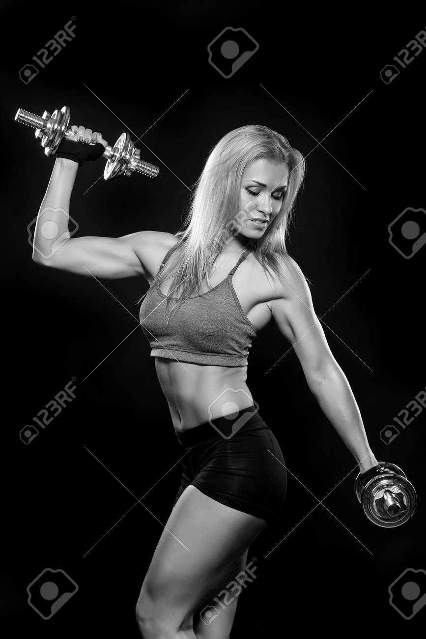 Athletic young woman doing workout with weights on dark background - 123614868