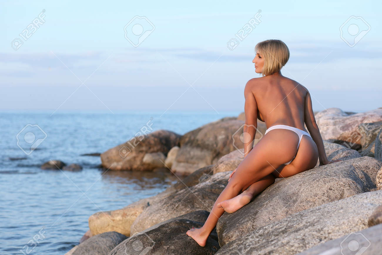 young athletic girl on the stone by the sea - 125116261