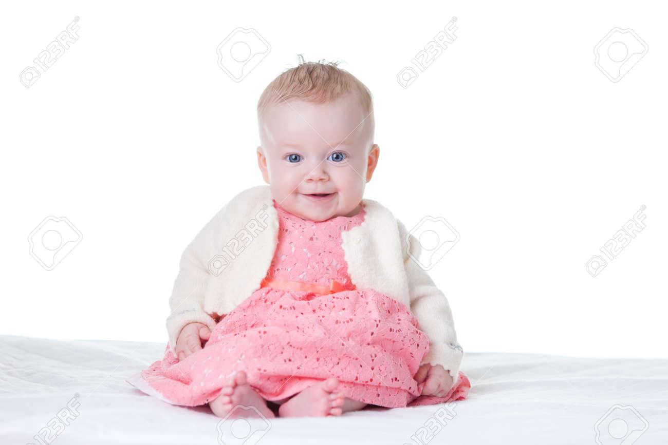 Kleine schattige baby meisje in roze jurk zittend geïsoleerde