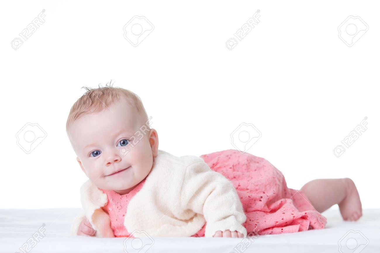 Schattige baby meisje in roze jurk op haar buik geïsoleerd