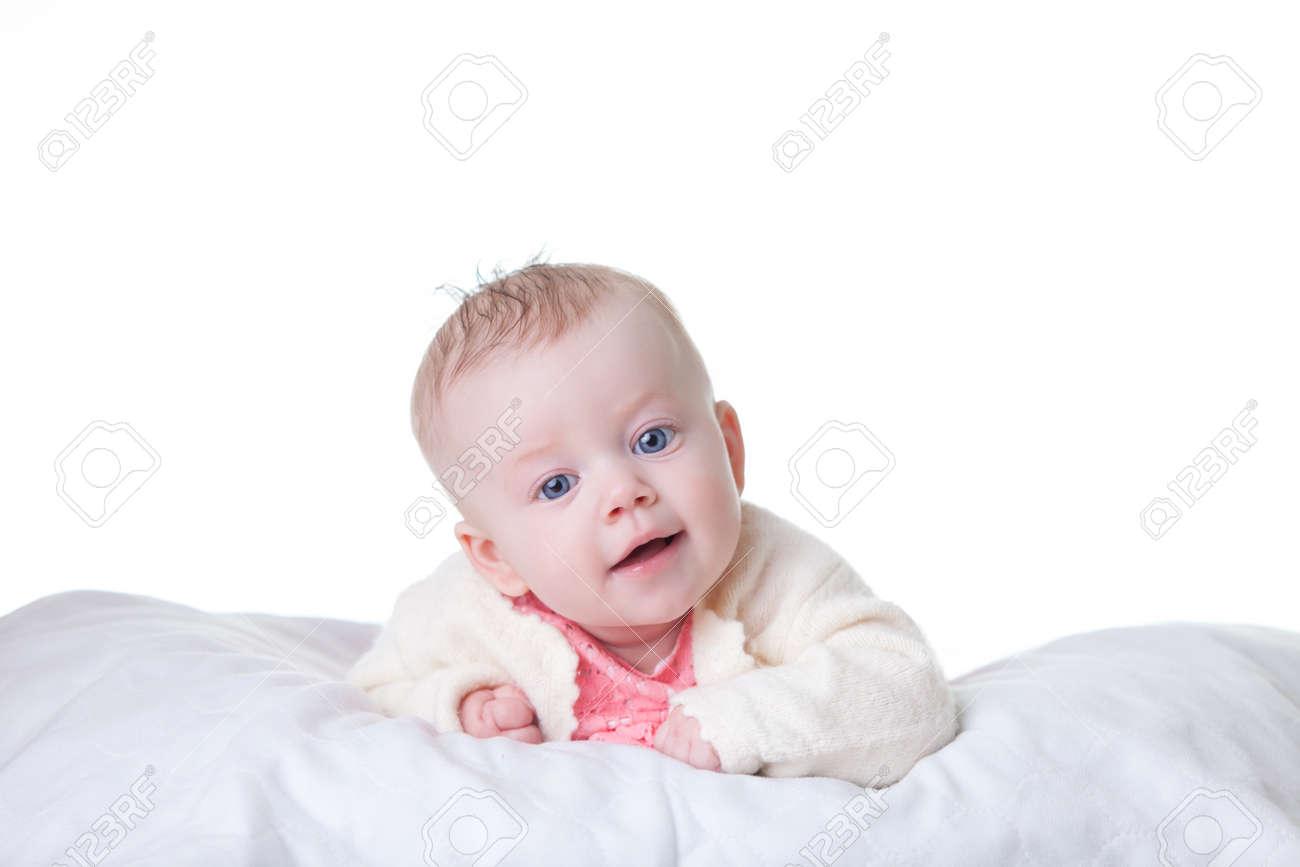 Schattige baby meisje in roze jurk op haar buik geïsoleerd royalty
