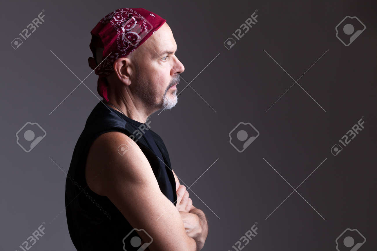 Mature biker in red bandana fold his hands, serious look, thinking