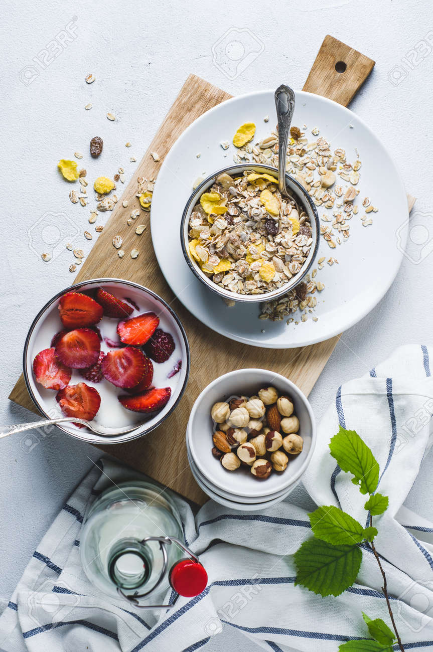 Muesli with fresh strawberries in a plate over a white concrete background - 83876194