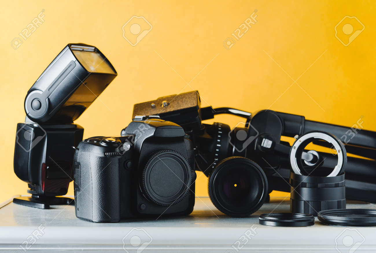 Digital camera, lenses and equipment of the photographer on a yellow background - 85167952