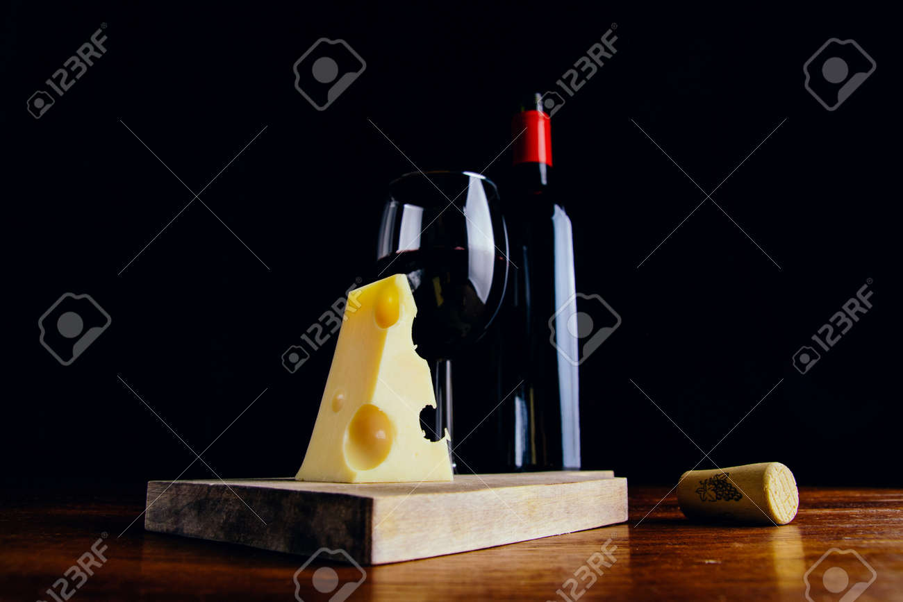 A glass of red wine, a bottle and a piece of cheese on a wooden table and a dark background - 151495021