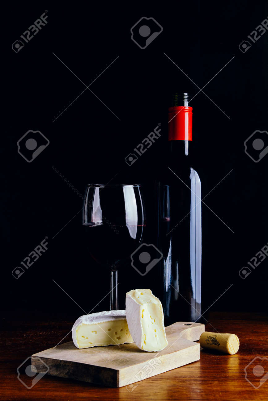 A glass of red wine, a bottle and a piece of cheese on a wooden table and a dark background - 151495201