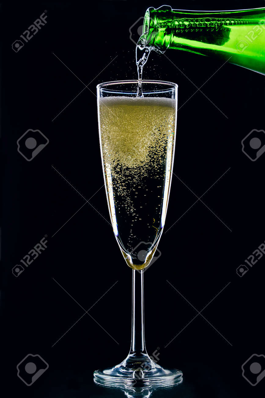 Sparkling wine pours from a bottle into a glass on a dark background - 152811659