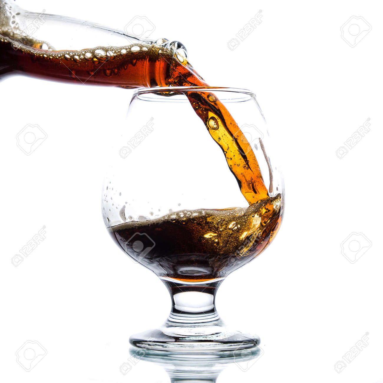 Brown ale pours from a bottle into a glass on a light background - 152811670