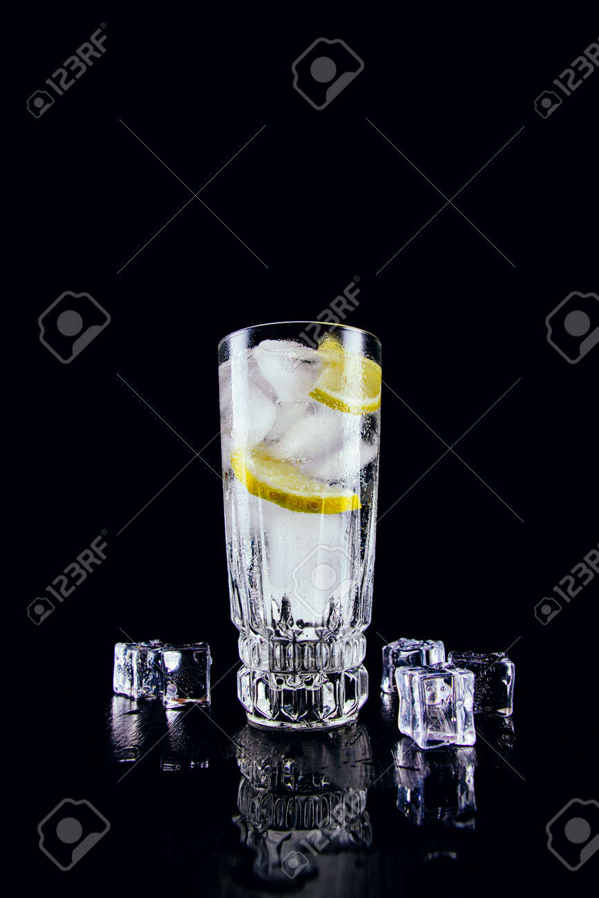 A glass of gin and tonic with lemon and ice cubes on black background - 152811673