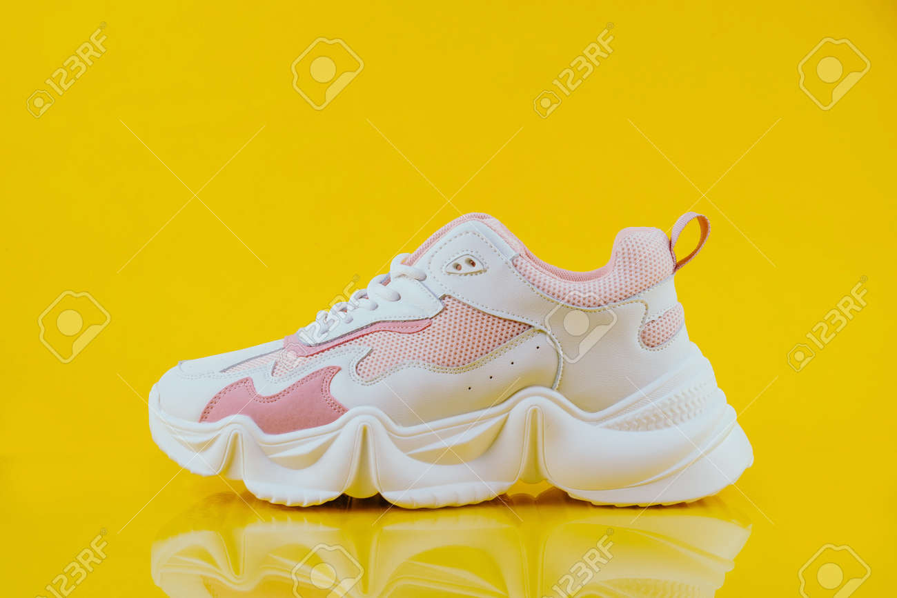 White and pink sports sneakers on an yellow background - 152811674