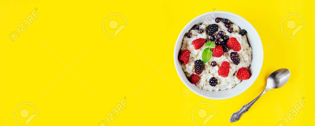 Oatmeal porridge with raspberries and blackberries in a light plate - 152811684