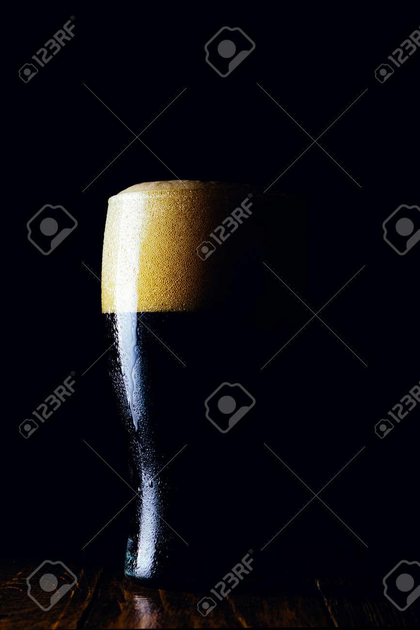 Porter beer mug with foam on a dark background - 152811685