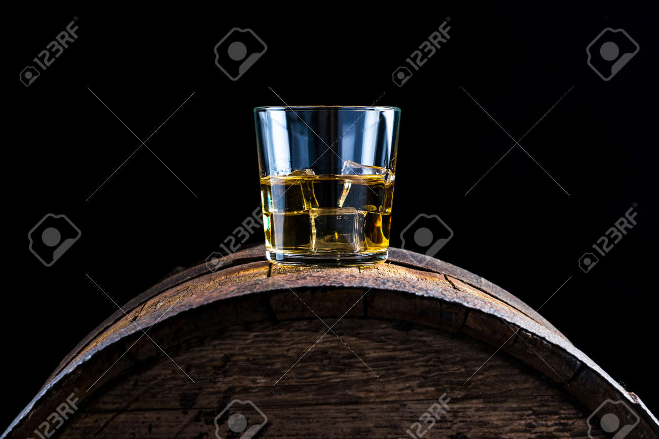 A glass of whiskey and ice cubes on an old wooden barrel - 152811736