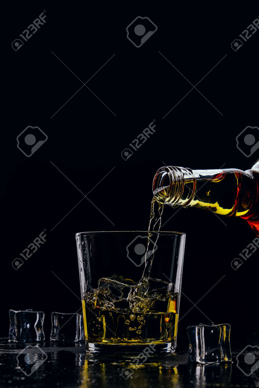 Whiskey pours from a bottle into a glass on a dark background - 152811744