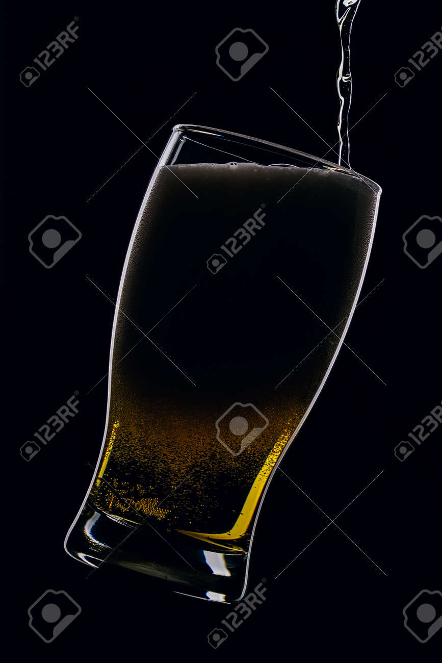 Lager beer pours from a bottle into a glass on a black background - 152811748