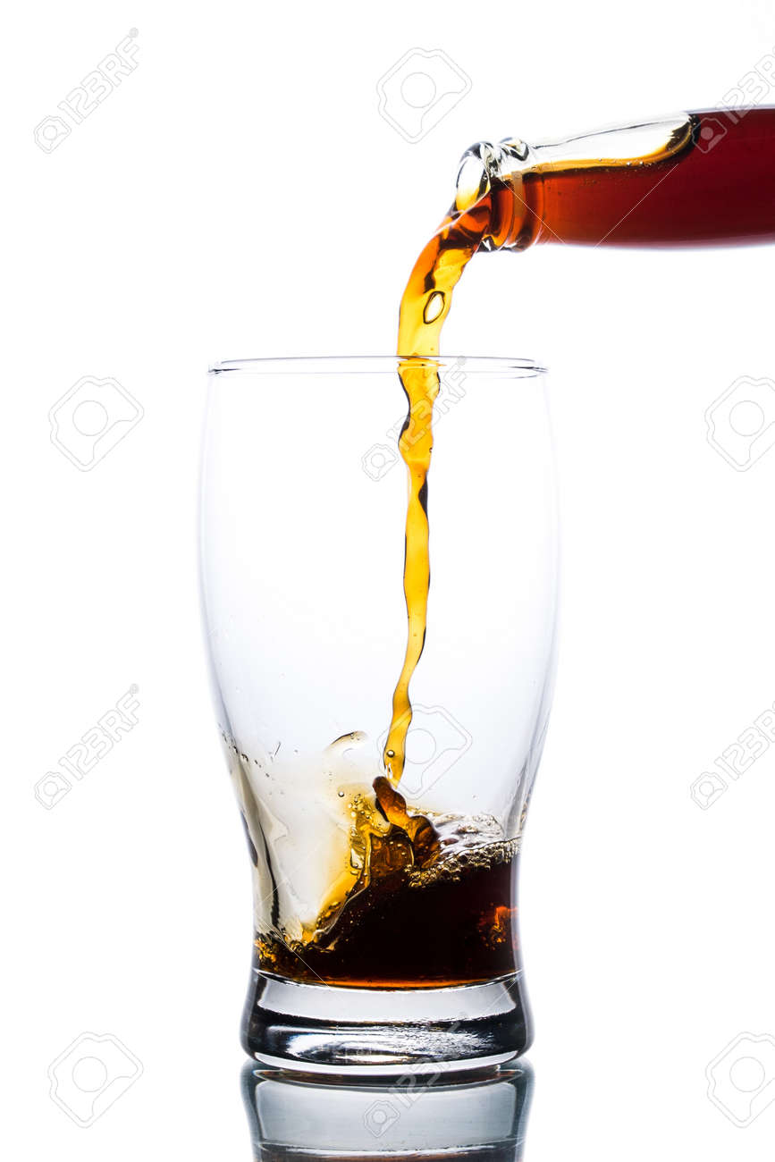Brown ale pours from a bottle into a glass on a light background - 152811752