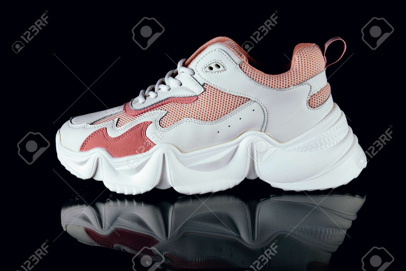 White and pink sports sneakers on an black background - 152811755
