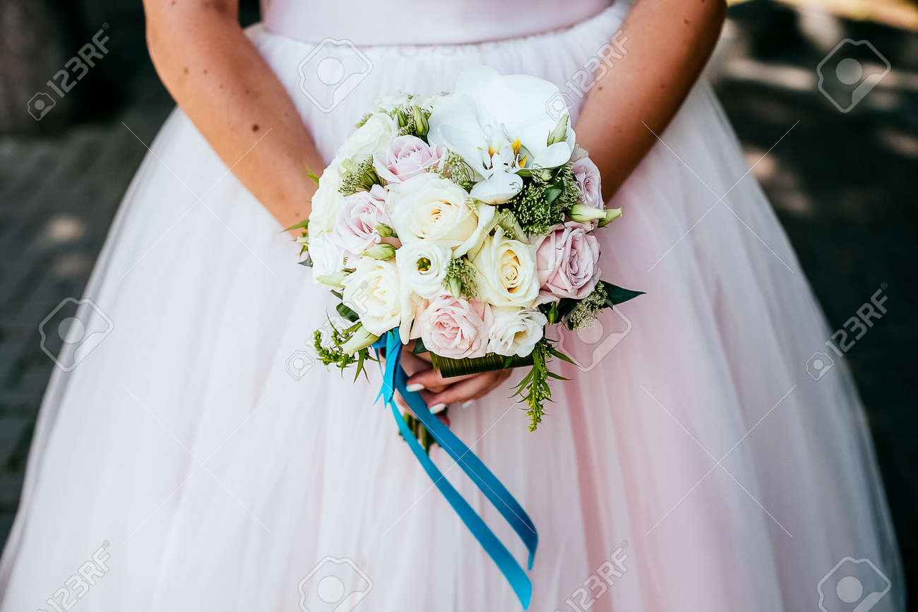 Bridal bouquet, hold the wedding bouquet in your hand, satin ribbons adorn the wedding bouquet of roses, on the background of the brides dress, fresh flowers, made by a florist - 153126538