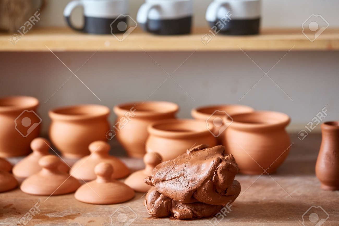 Ceramic Dishware On Worktop And Shelves With Piece Of Clay In Stock Photo Picture And Royalty Free Image Image 99719241