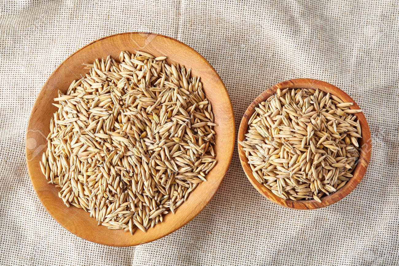 Oat groats or oat spike in wooden plate on homespun tablecloth,