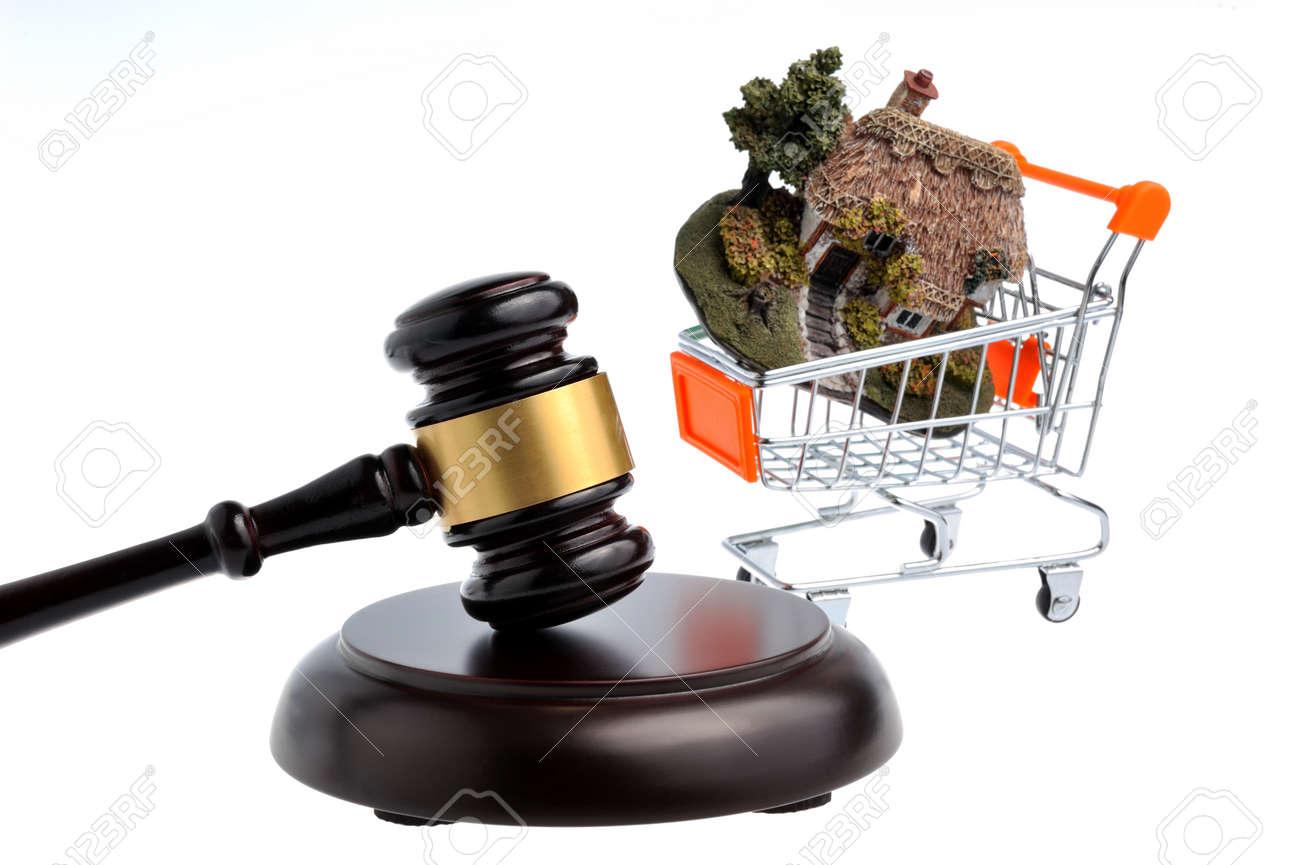 Trolley In Huis : Hamer van de rechter met model van huis in trolley geïsoleerd op