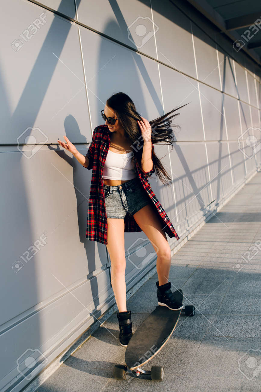 Pretty young fashion sexy swag girl riding wooden longboard on..