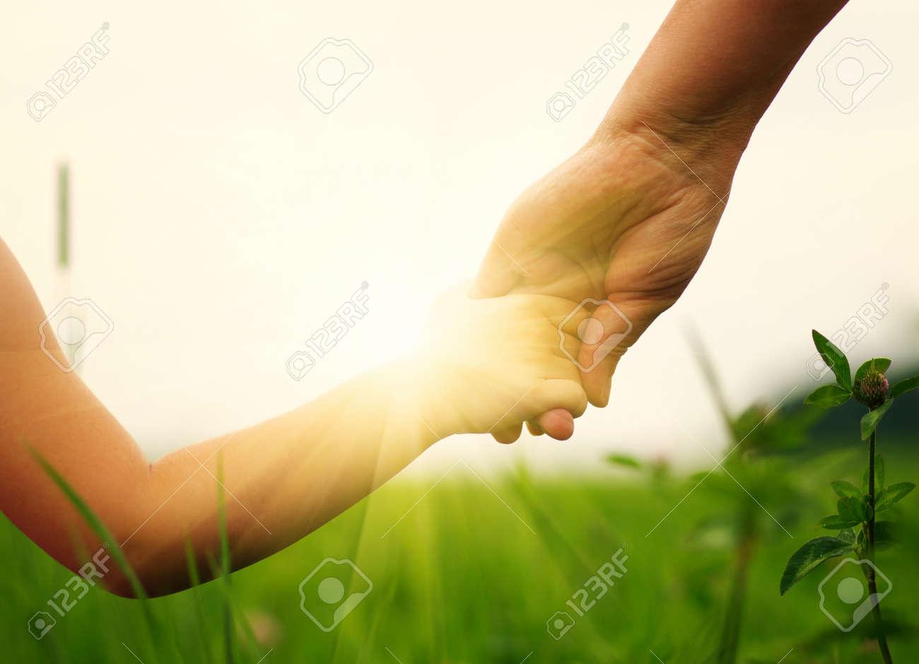 Mains de la mère et la fille se tenant sur le champ Banque d'images - 49025614