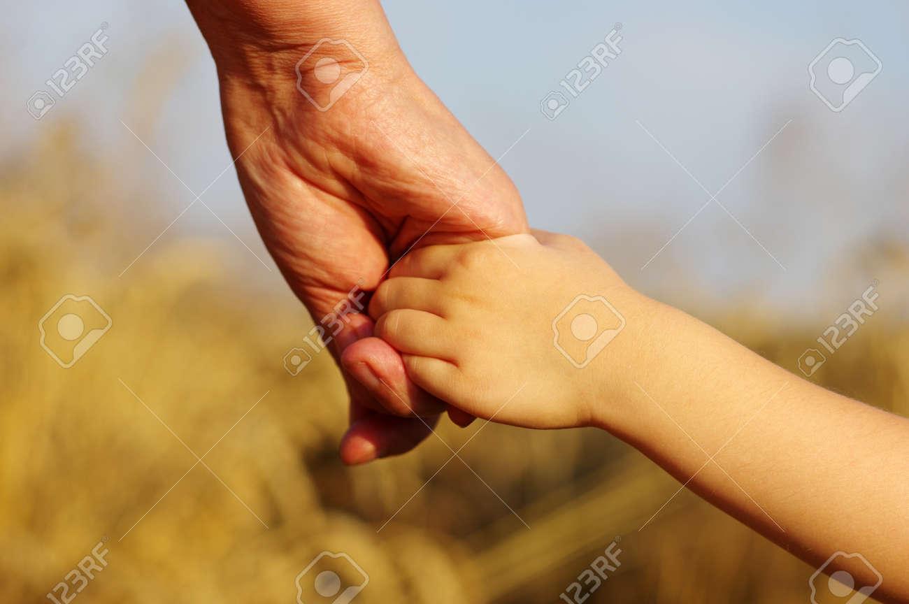 Mains de la mère et la fille se tenant sur le champ Banque d'images - 49026461